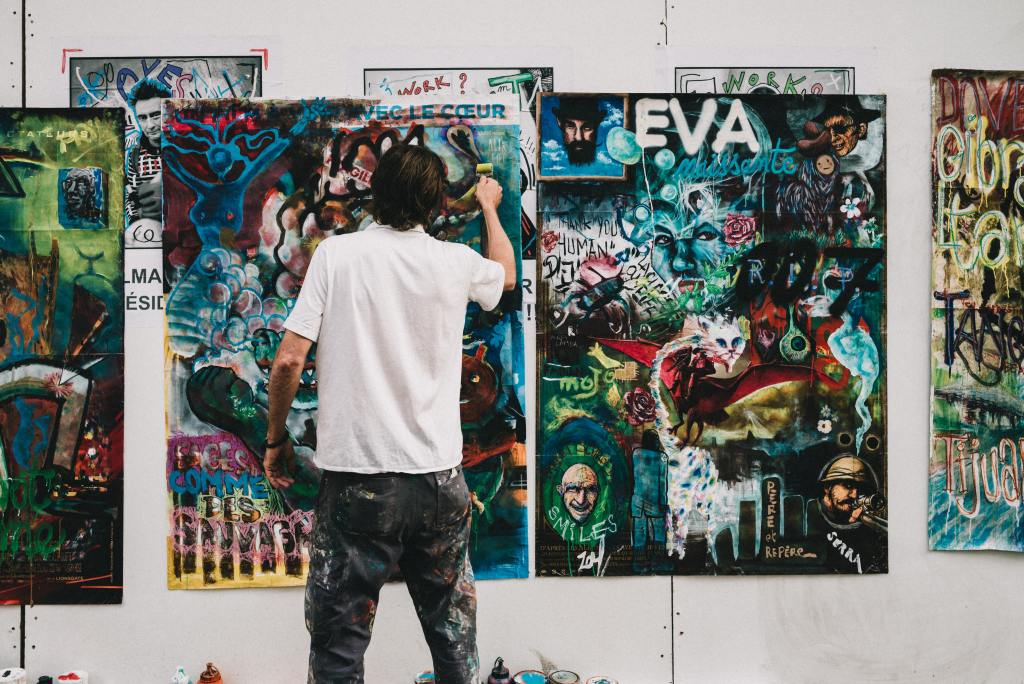 Man in front of several graffiti paintings painting one of them