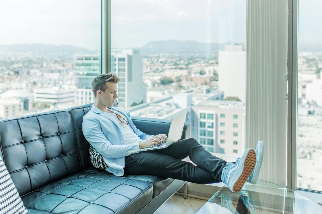 Young man sitting comfortably on couch working on laptop