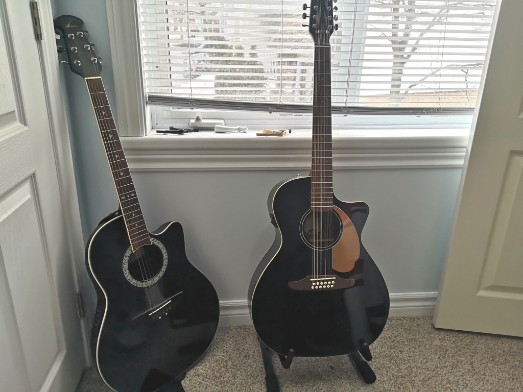 Two acoustic guitars next to each other