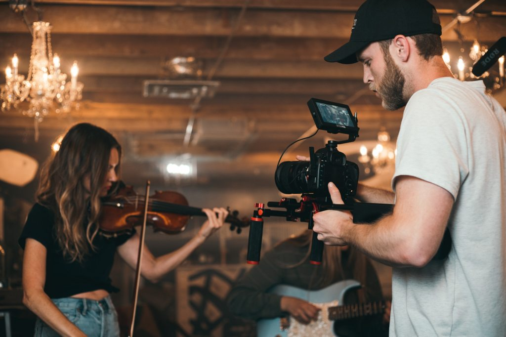 Camera man filming young woman playing fiddle
