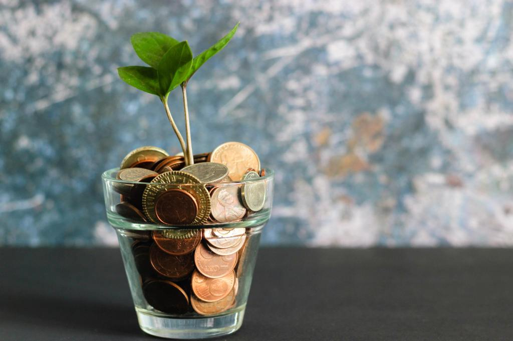 Glass cup of money with stem and leaves growing out of it