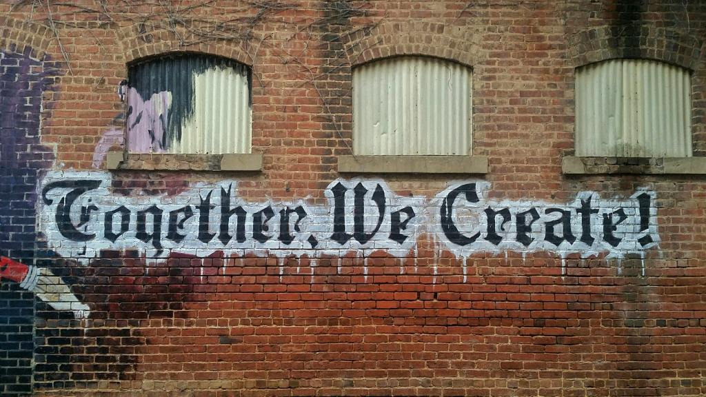 Grafitti on brick wall of text Together We Create