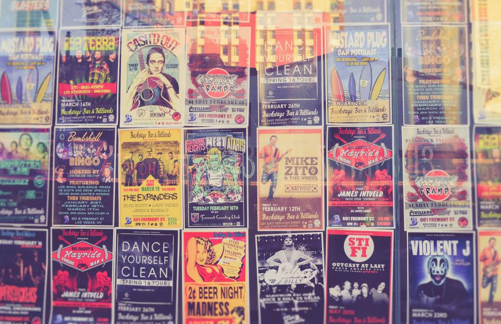 Wall covered in various posters for upcoming concerts