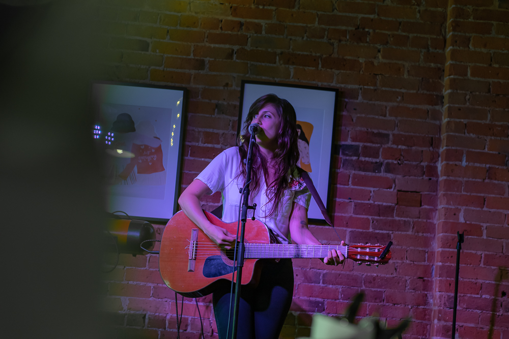 Katey Gatta performing solo with an acoustic guitar
