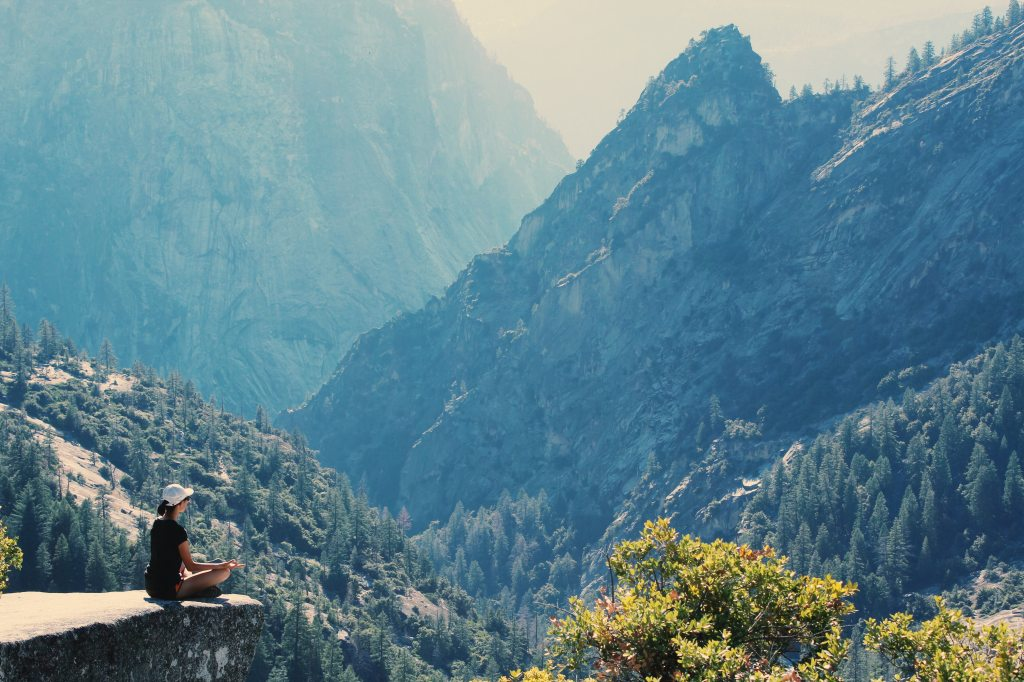 Young woman sitting in yoga pose on the edge of a rock in the mountains