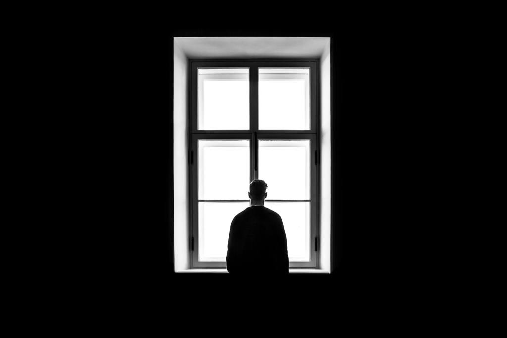 Silhouette of a man in front of a white window