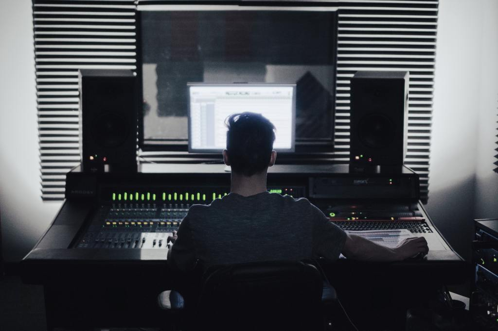 Man sitting in front of mixing board, speakers and computer screen