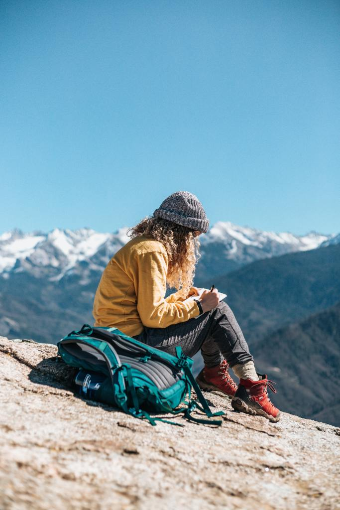 Girl sitting outside on a rock writing in a notebook