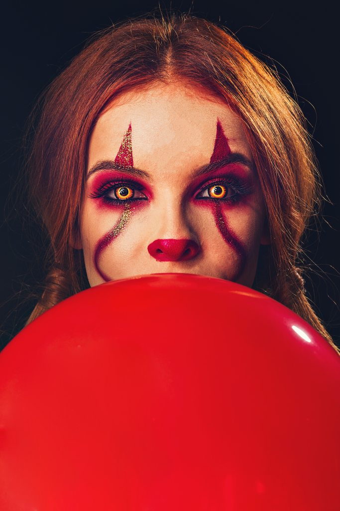 Girl holding red balloon dressed as Stephen King's Pennywise the dancing clown