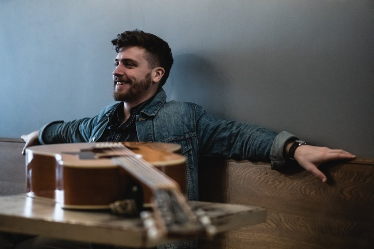 Kyler Tapscott smiling with acoustic guitar on table