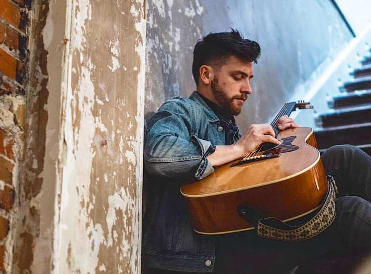 Kyler Tapscott with an acoustic guitar