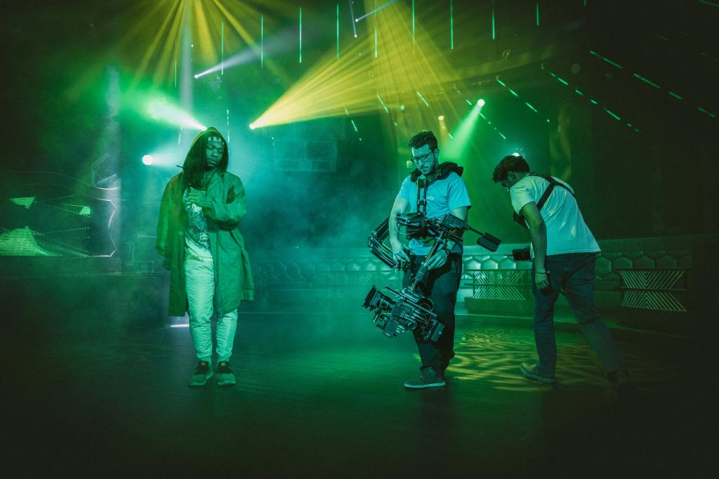 Music video crew shooting a video on stage with green lighting