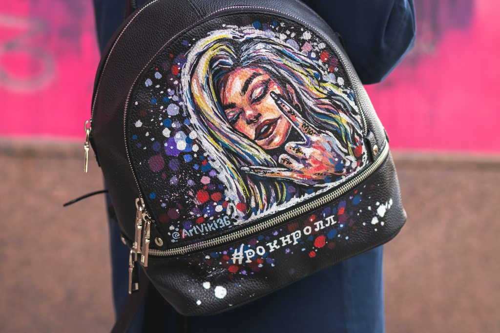 Colorful art of woman's face painted on a purse