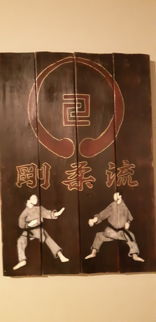 Wood sign with Japanese text, two karate fighters in karate poses