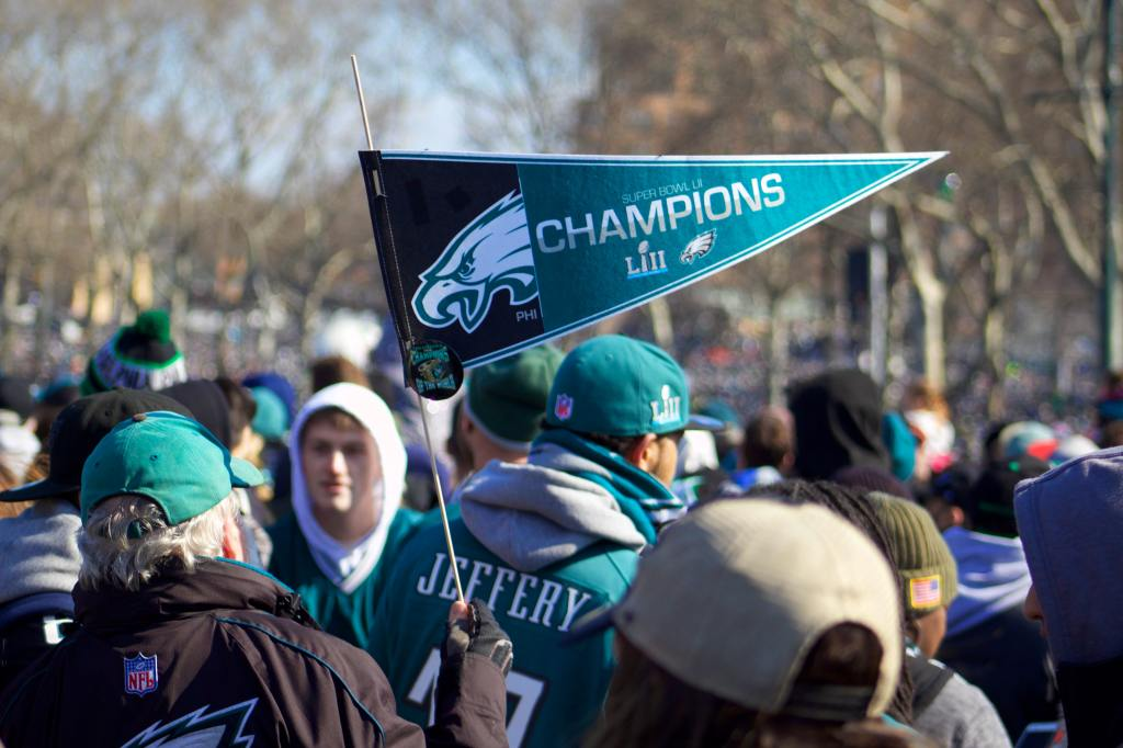 Sports fans in Philadelphia Eagles gear crowd the streets waving flags celebrating their Super Bowl LII win