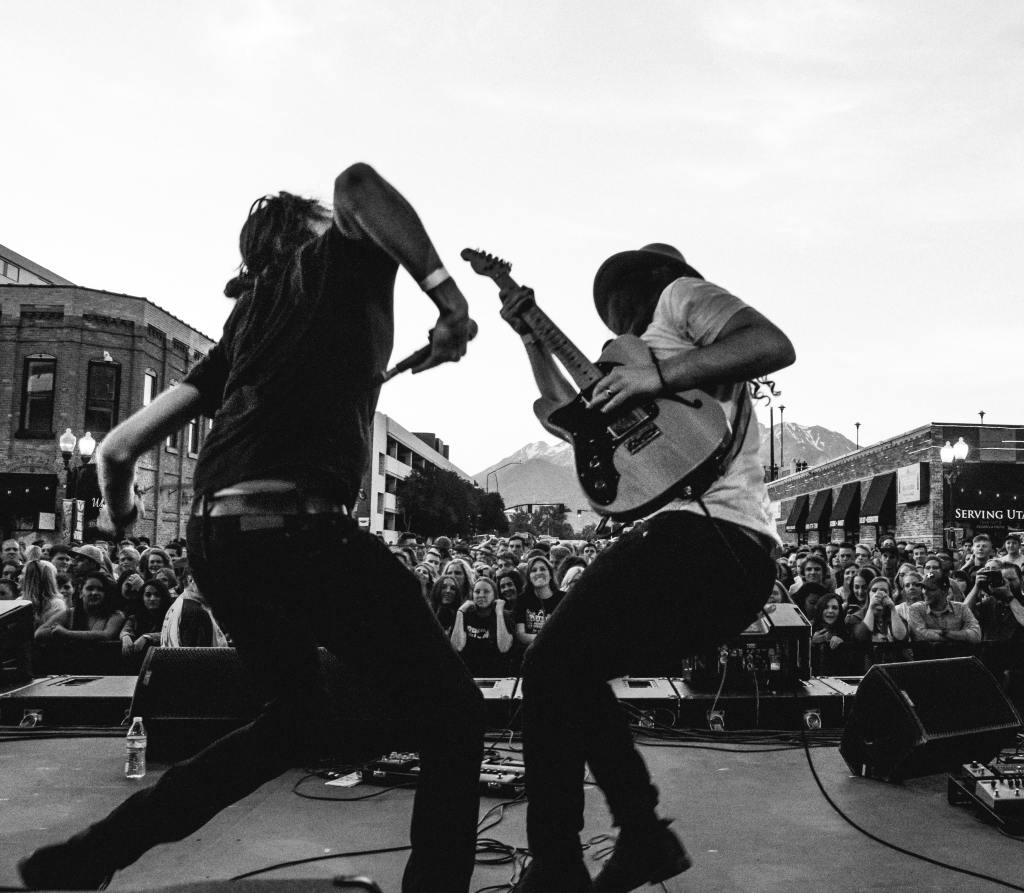 Black and white photo of musicians performing in front of big crowd in the street